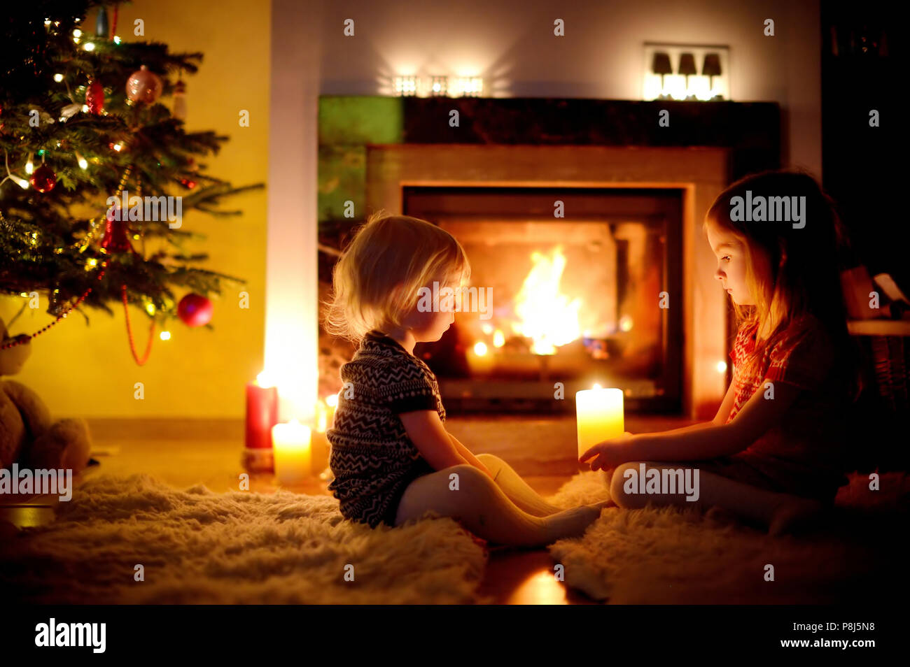 Two Cute Little Sisters Sitting By A Fireplace Holding