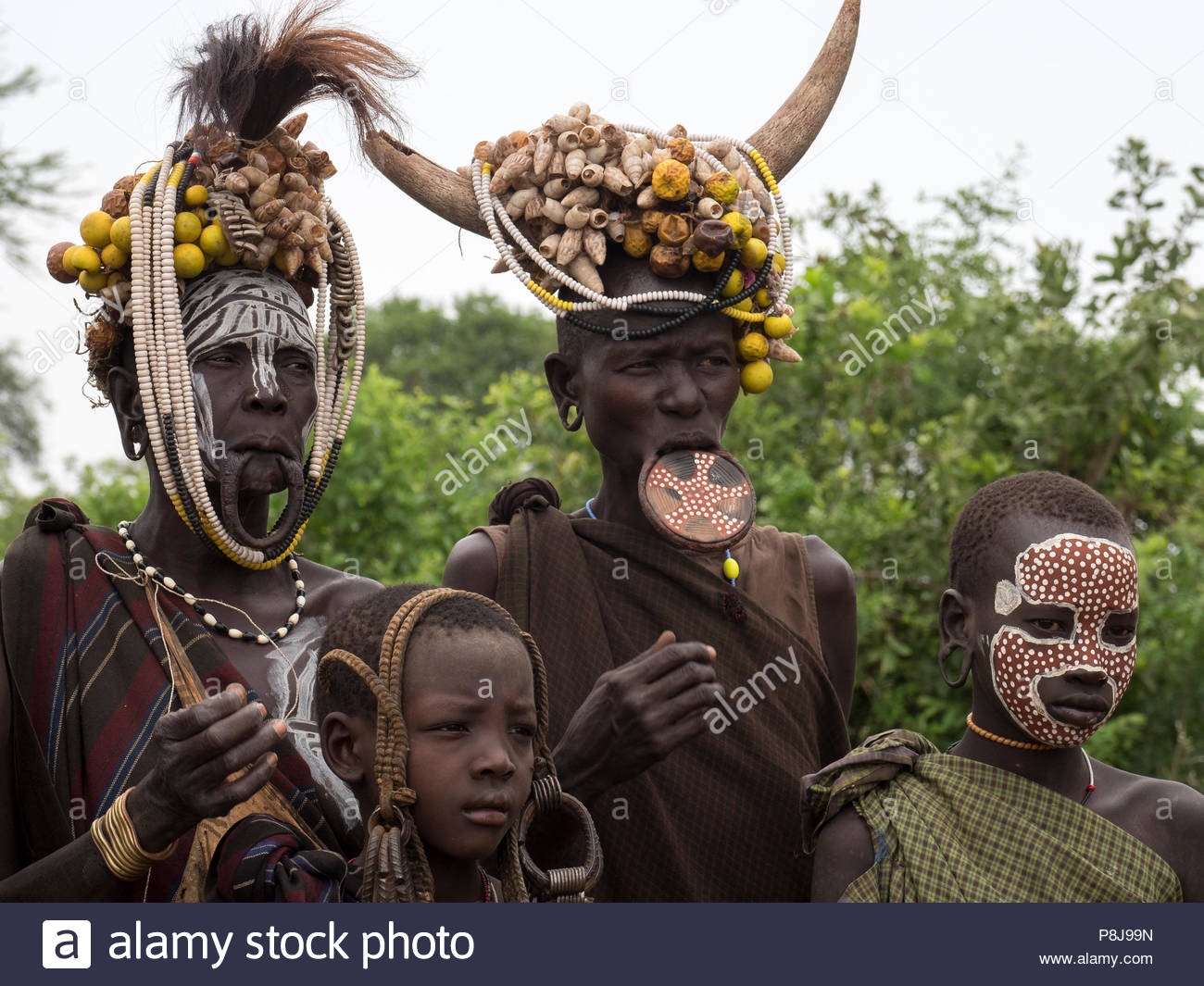 Women and children of the Mursi tribe with headdress and lip plate, Ethiopia - Stock Image