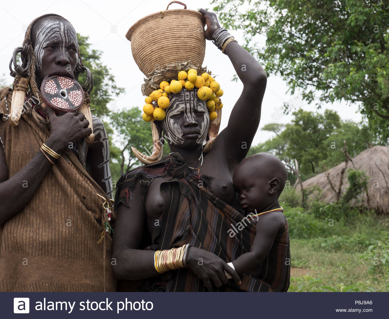Women with infants from the Mursi tribe, with lip plates and headdress, Ethiopia - Stock Image