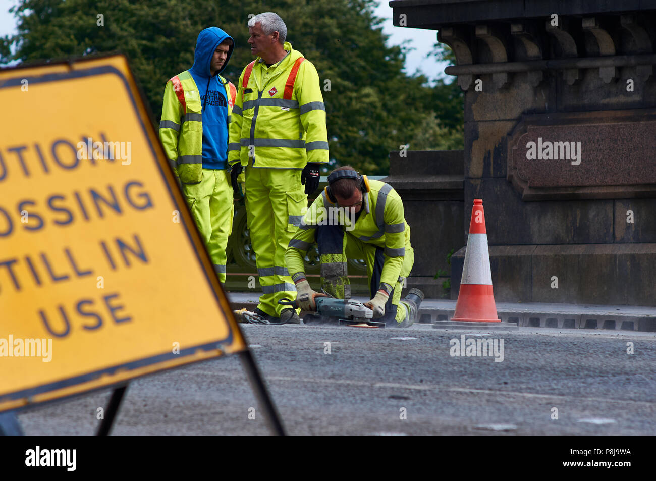 A road maintenance worker using an angle grinder power tool to finish off the road surface repairs. Worker is wearing ear defenders and high-vis top. - Stock Image