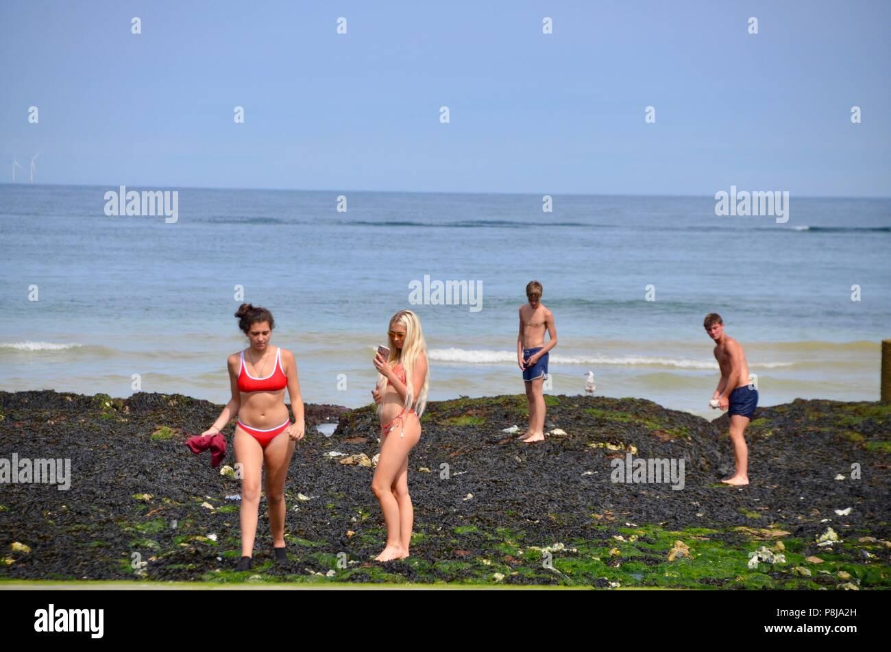 women in bikinis taking selfies on beach broadstairs kent UK - Stock Image