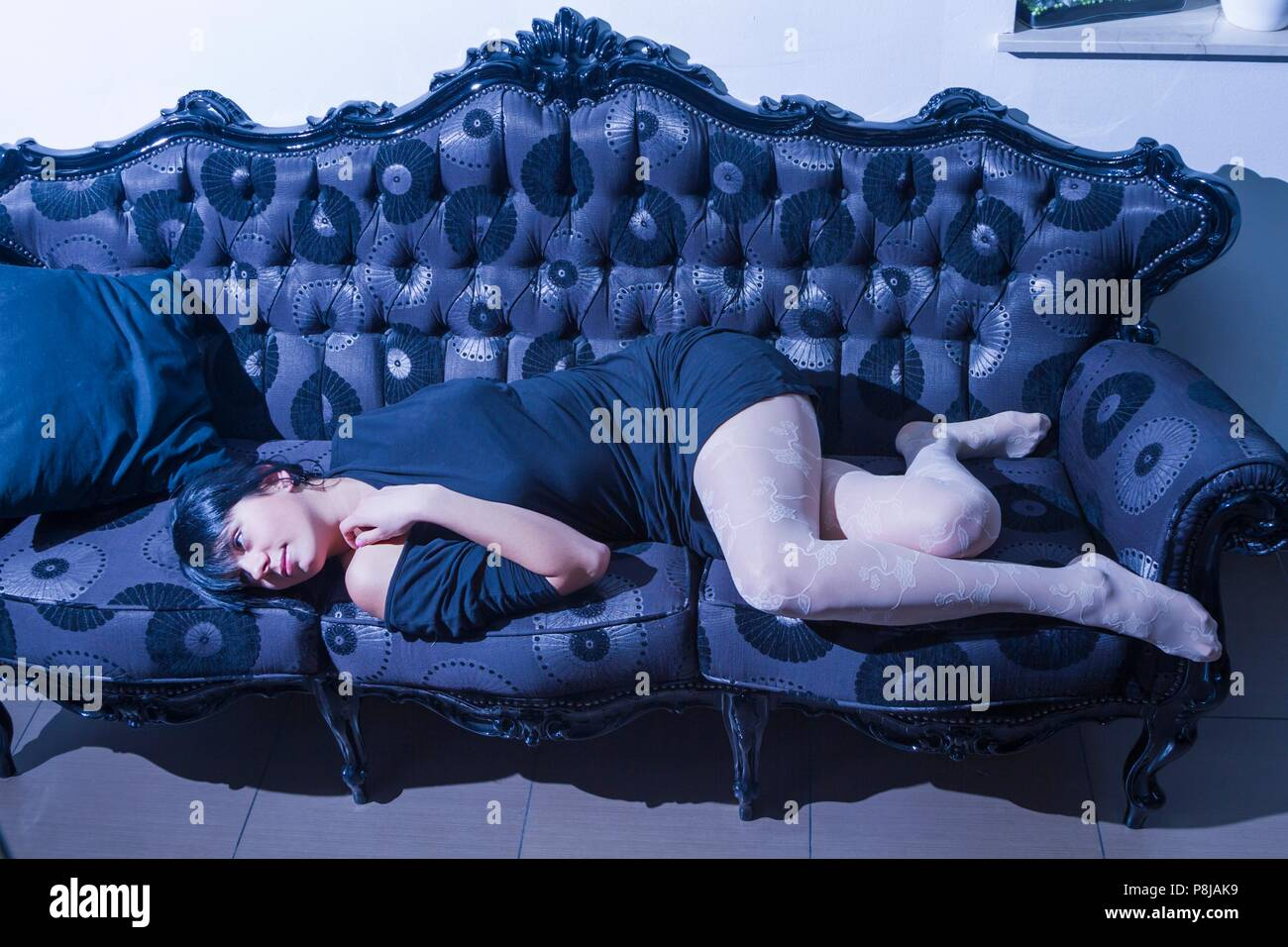 Lying indoors at night after coming home aftermath lifestyle - Stock Image