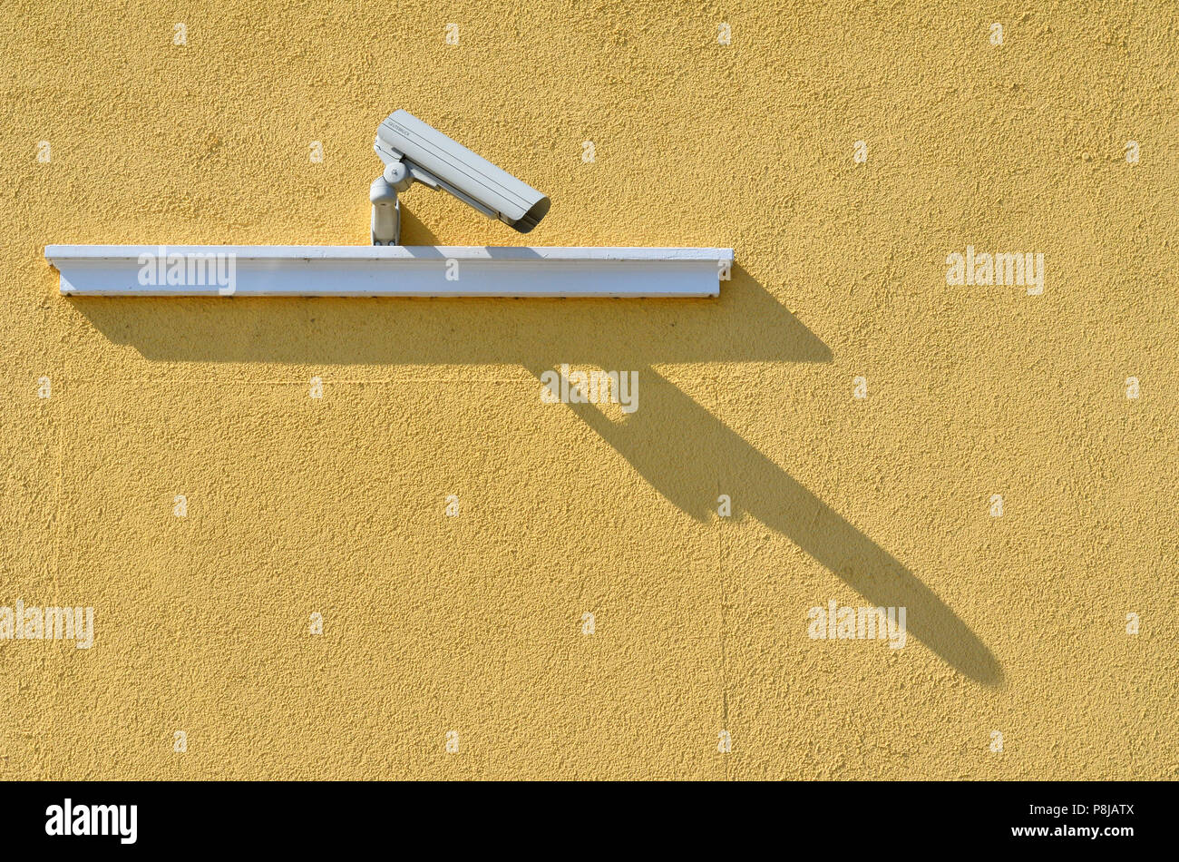 surveillance camera with shadow mounted on a yellow wall and looks down. Brother is watching you. - Stock Image