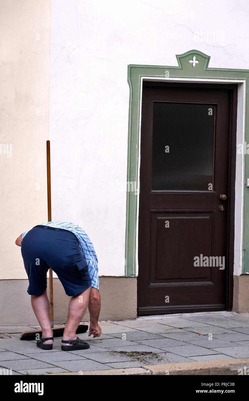 A man cleans the walkway. Garmisch-Partenkirchen. - Stock Image