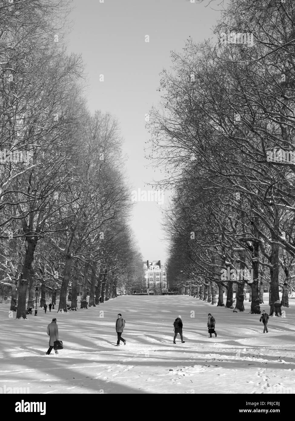 London Park, snow scene, workers commuting through snow - Stock Image