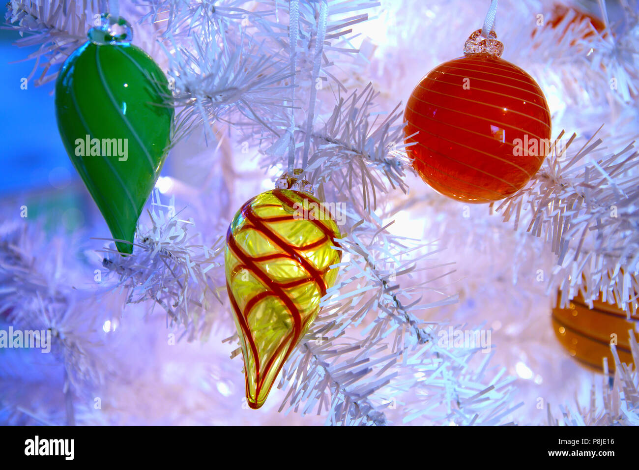 blown glass decorations hanging on a white christmas tree with twinkle lights strung throughout