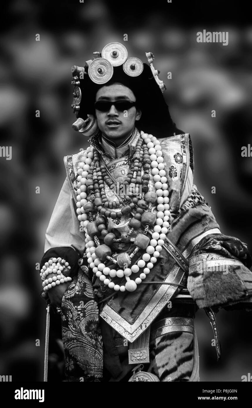 Male Khampa wears tiger skin, coral, zee stones & gold gau boxes at the Litang Horse Festival - Sichuan Province, China, (Tibet) - Stock Image