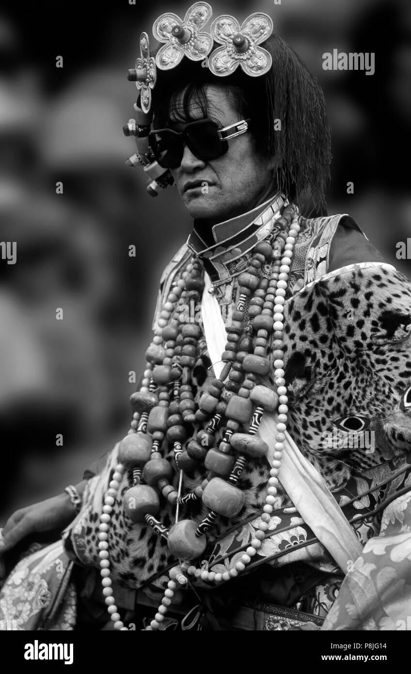 Male Khampa wears leopard skin, coral, zee stones & gold gau boxes at the Litang Horse Festival - Sichuan Province, China, (Tibet) - Stock Image