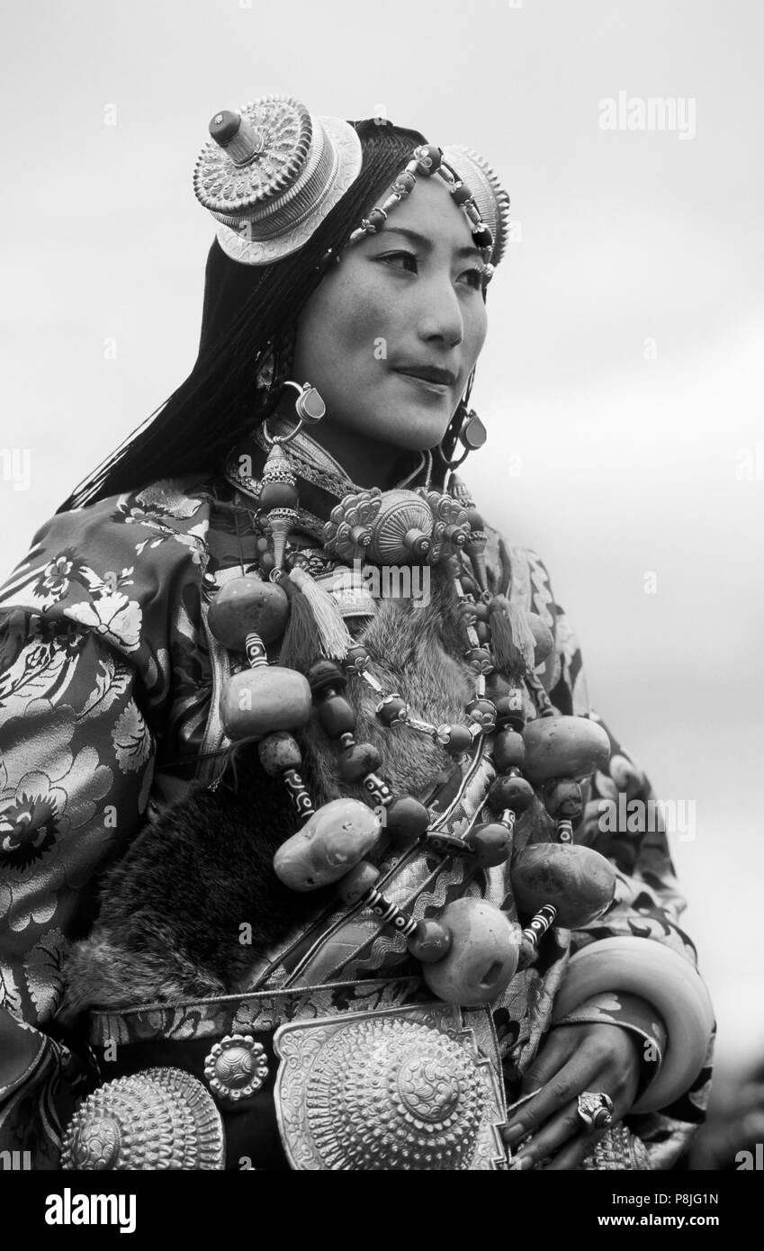 Female Khampa wears gold hair pieces & gau boxes, zee stones & coral at the Litang Horse Festival - Sichuan Province, China - Stock Image