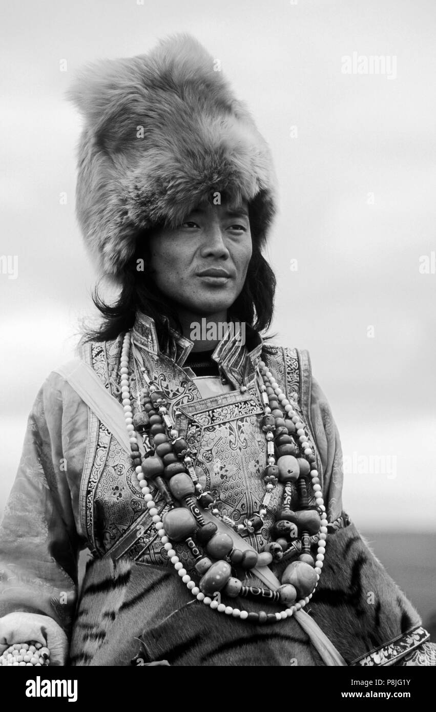 Male Khampa wears coral, zee stones, fox fur hat & tiger skin at the Litang Horse Festival - Sichuan Province, China, (Tibet) - Stock Image