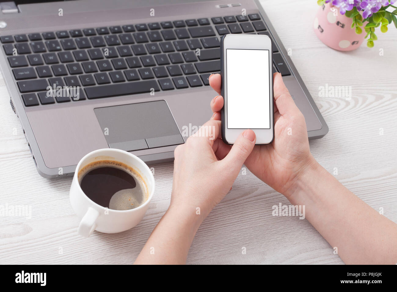 A woman holds smartphone white phone in the workplace in the room. Woman using a mobile phone for work. - Stock Image