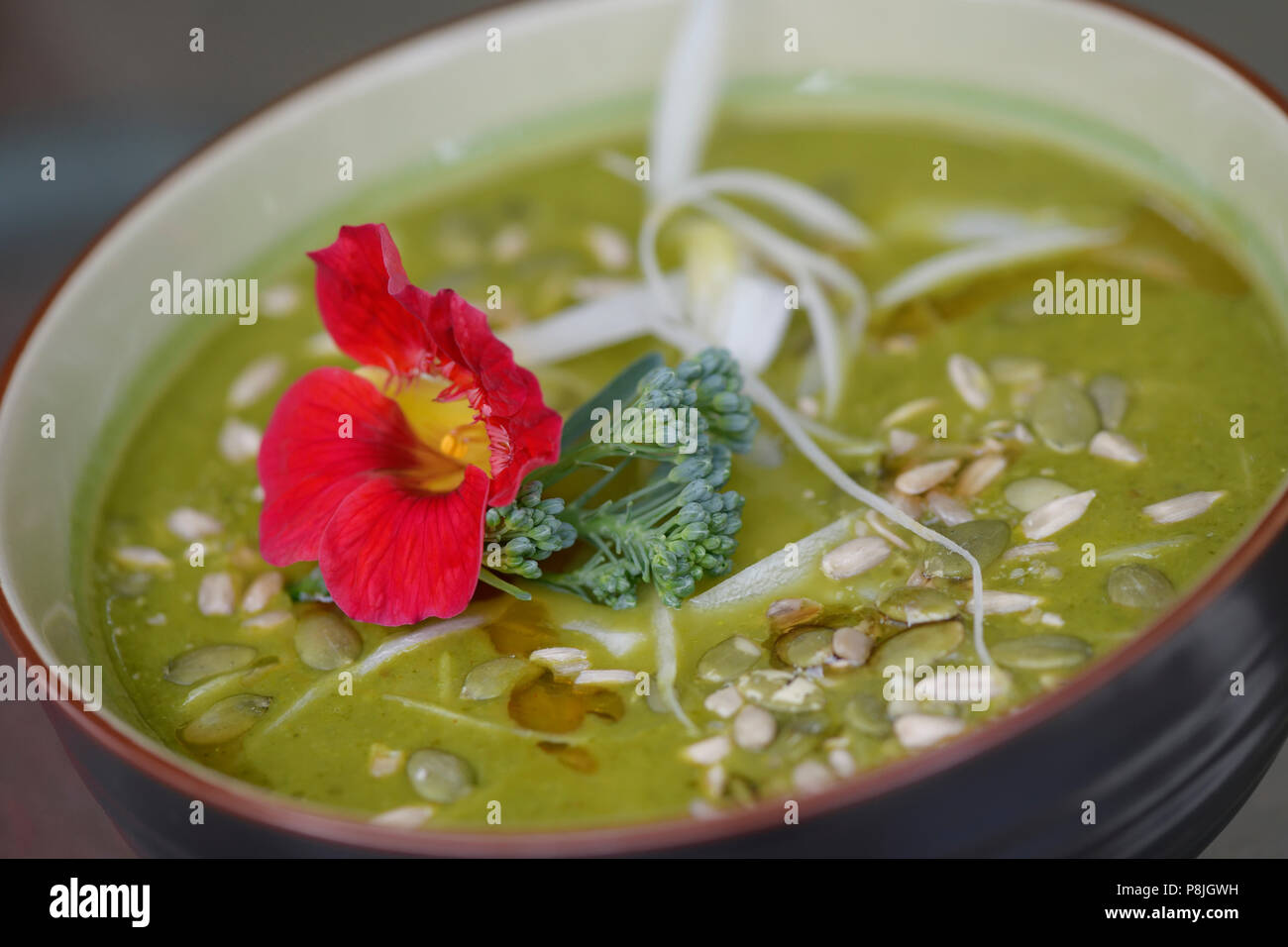 A bowl of healthy Green Goddess home-made soup made of freshly pureed organic greens and vegetables decorated with Nasturtium and pumpkin seeds Stock Photo