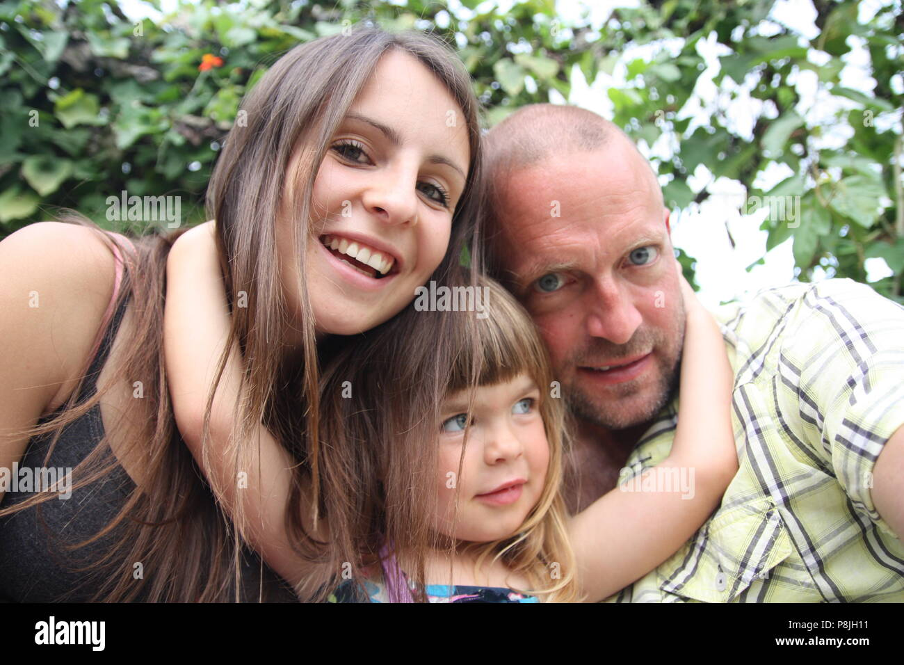 Beautiful happy family cuddling selfie picture long dark hair couple with toddler - Stock Image