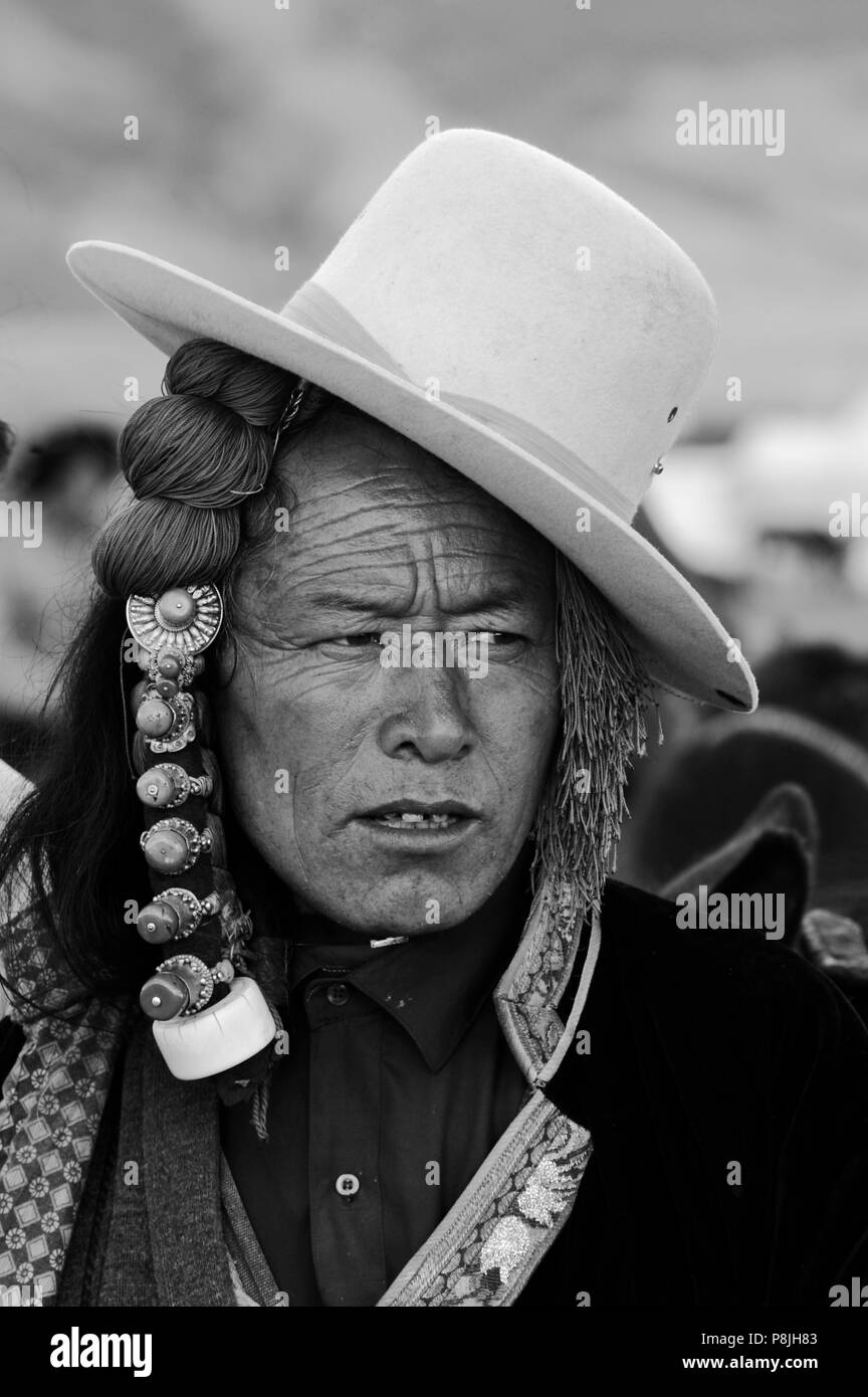 Khampa with jaunty cowboy hat and ivory hair peices at the  Litang Horse Festival  in Kham - Sichuan Province, China, (Tibet) - Stock Image