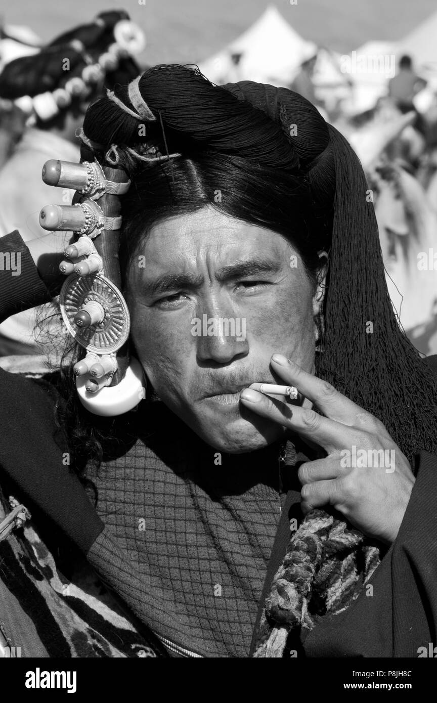 Khampa man with gold & coral hair peices smokes at the Litang Horse Festival - Kham, Sichuan Province, China, (Tibet) - Stock Image