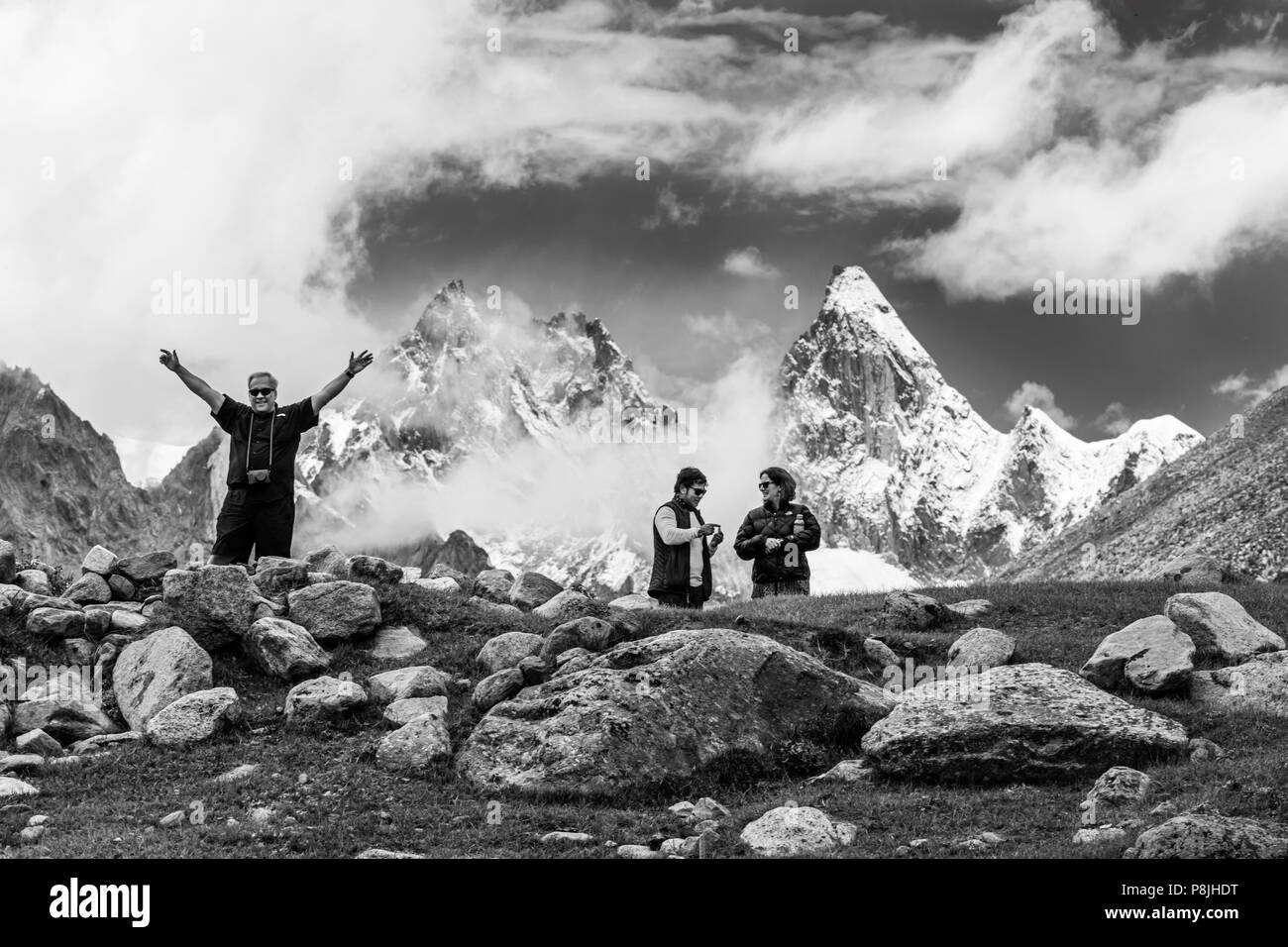 Travelers infront of the  massive himalayan peaks of NUN and KUN which reach a height of23,409 feet - ZANSKAR, LADAKH, INDIA - Stock Image