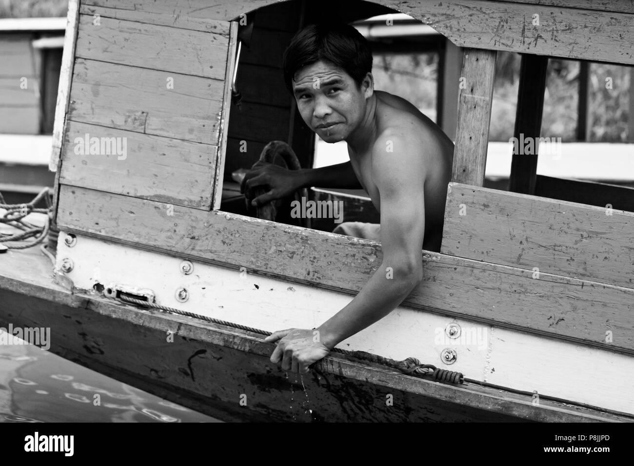 LAOTIAN man drives a boat on the MEKONG RIVER- LUANG PRABANG, LAOS - Stock Image
