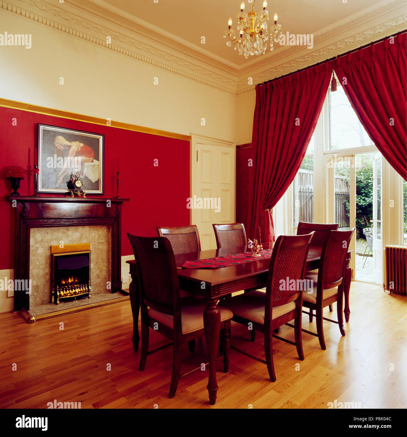 Red curtains and wooden flooring in dining room with ...