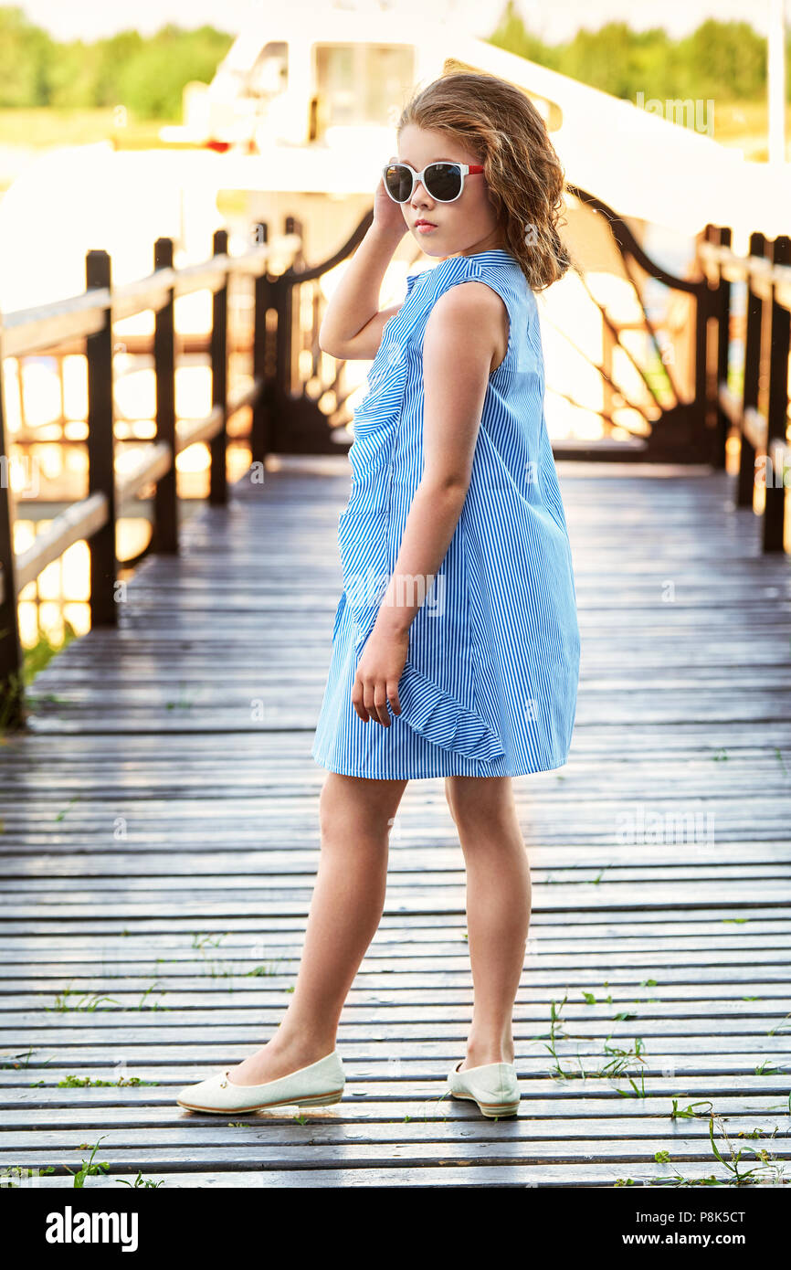 02272c716 Pretty little girl elegant blue dress for teenager resting on bridge pier.  Beautiful child wears summer clothing, sunglasses. Fashion kid concept.
