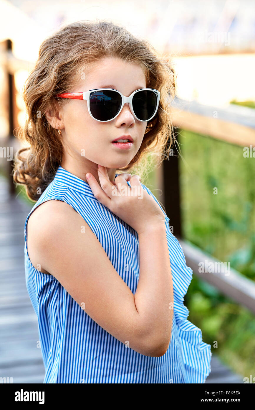 f56a85d2a Elegant child portrait. Little girl model wearing summer cool clothing,  sunglasses. Marine style