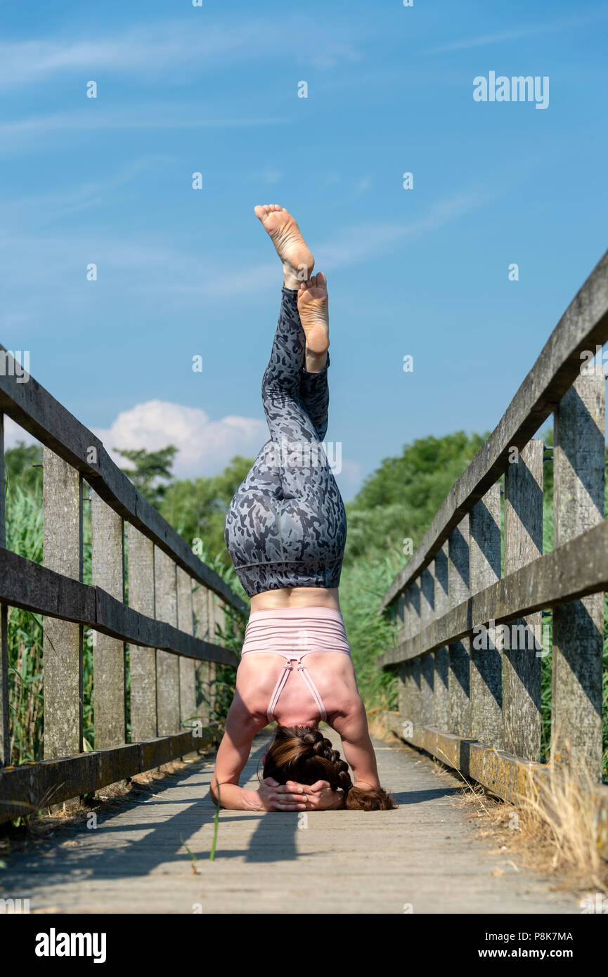 woman practicing yoga doing a headstand with eagle legs, outdoors on a wooden bridge. - Stock Image