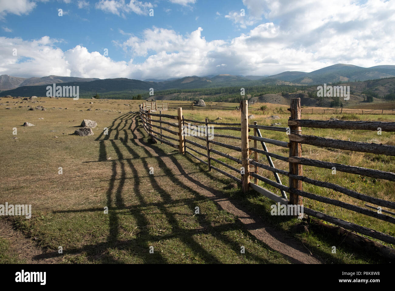 Wooden fence in the highlands and blue sky with clouds - Stock Image