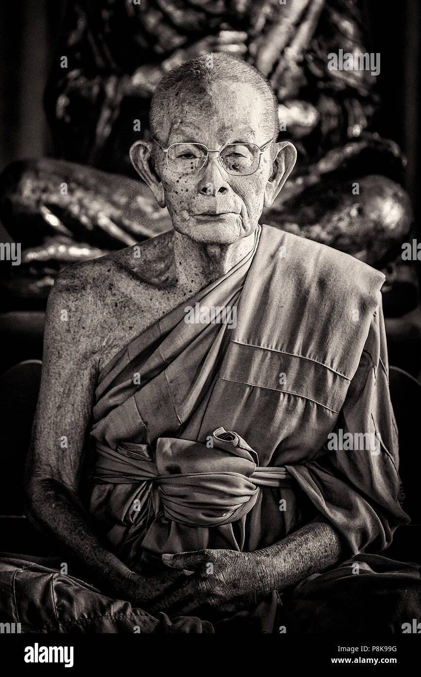 A portrait of an elderly male monk meditating in a temple in Thailand. - Stock Image