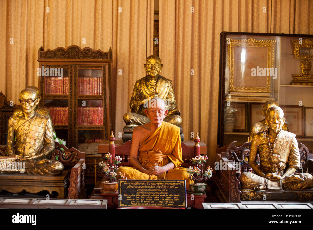 An elderly male monk meditating in a temple in Thailand. - Stock Image
