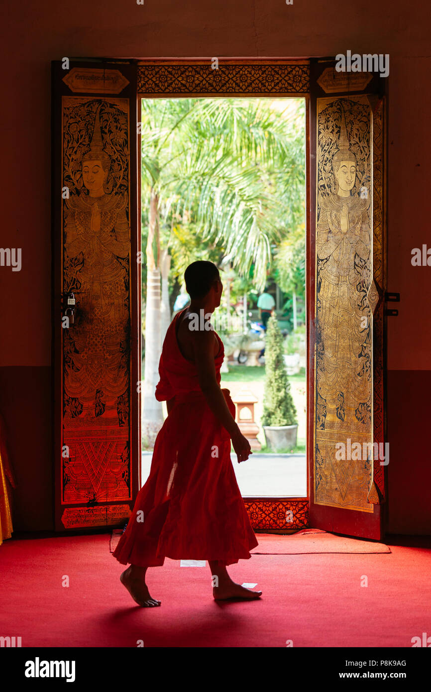 A monk in traditional robes walks past a door in a Buddhist temple in Thailand. - Stock Image