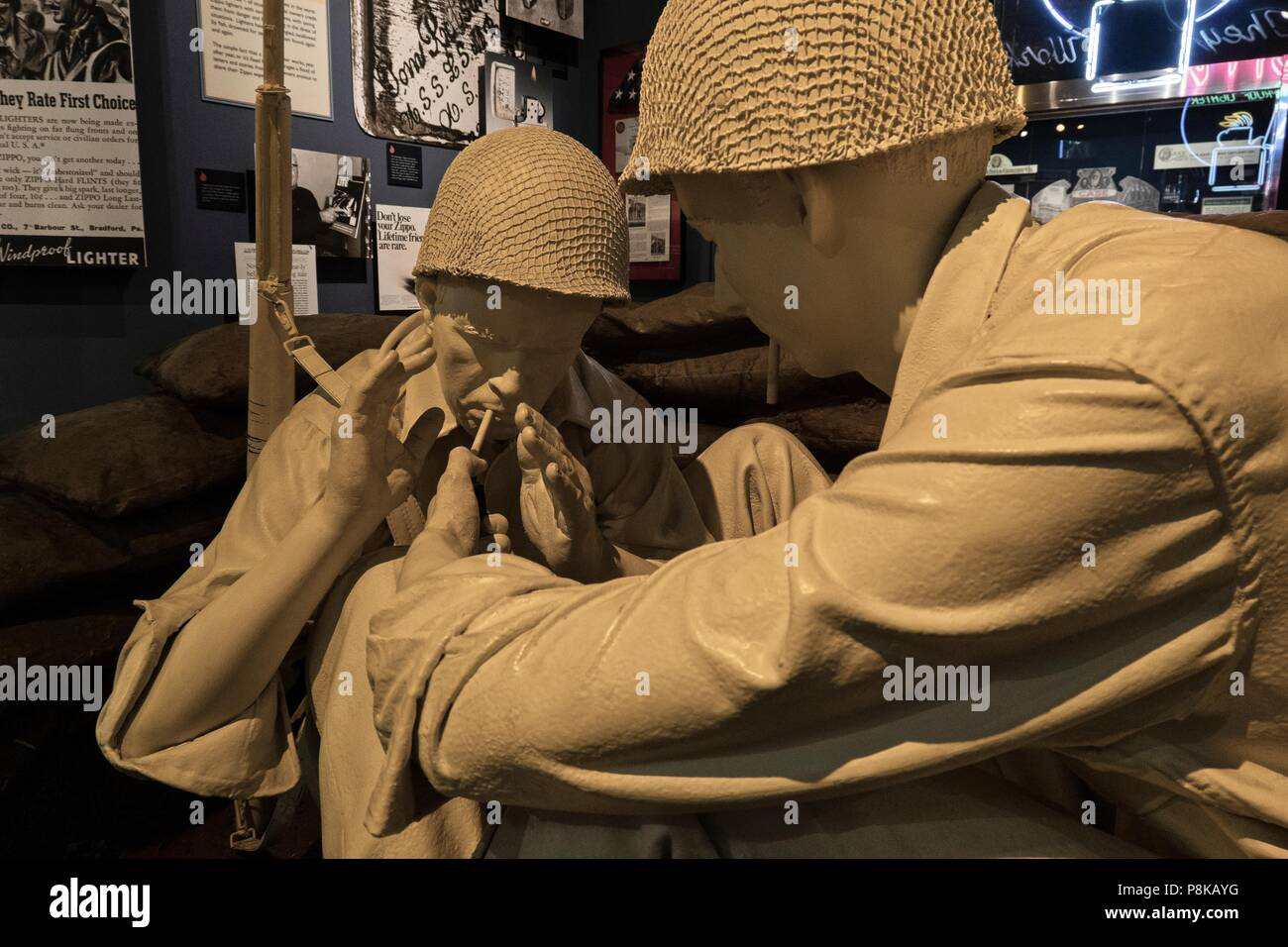 A statue of two World War II infantry man sharing a smoke and using a zippo lighter is showcased at zippo Museum in Bradford Pennsylvania - Stock Image