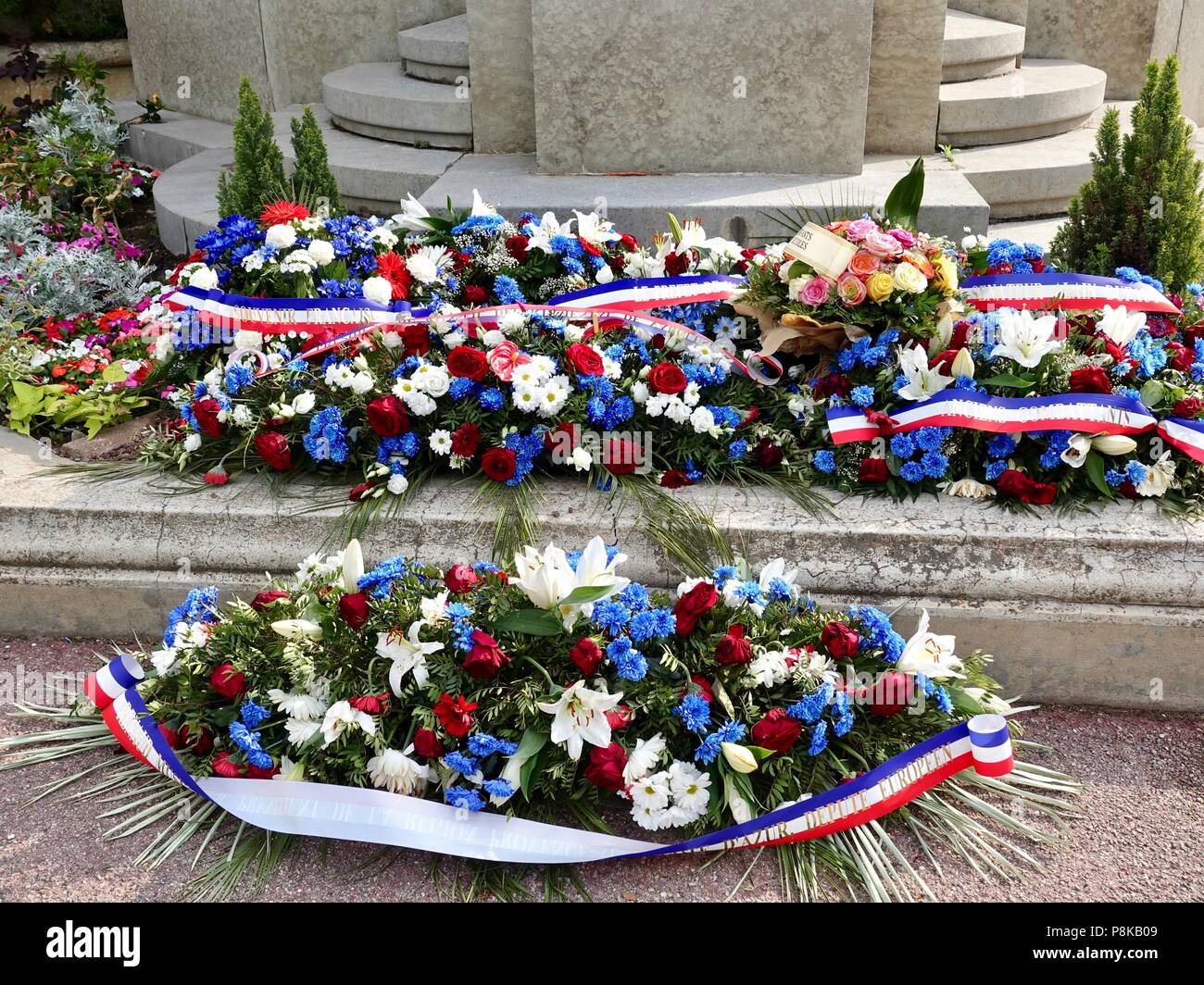 Blue, white, and red flowers with ribbons, placed in front of a French war memorial in honor of those who died fighting for France, Avignon, France. - Stock Image
