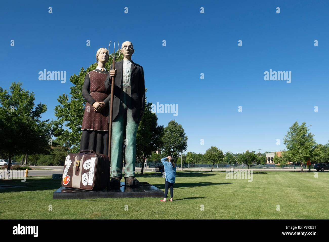 A tourist looking at Seward Johnson's 25 foot statue 'God Bless America' in Elkhart Indiana's Central Park. It is a 3-dimensional re-creation of the i - Stock Image
