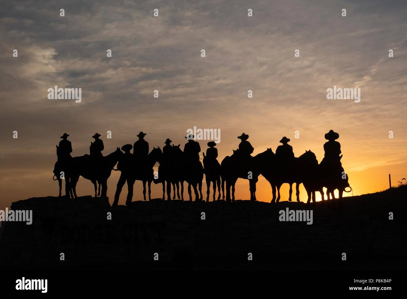 silhouette sculpture of cowboys on horseback  at sunset in Dodge city, Kansas - Stock Image