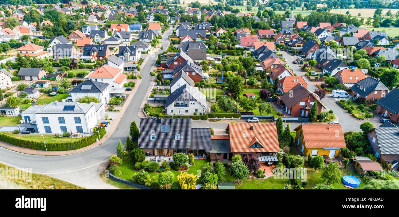 Typical German new housing development in the flat countryside of northern Germany between a forest and fields and meadows, made with drone - Stock Image