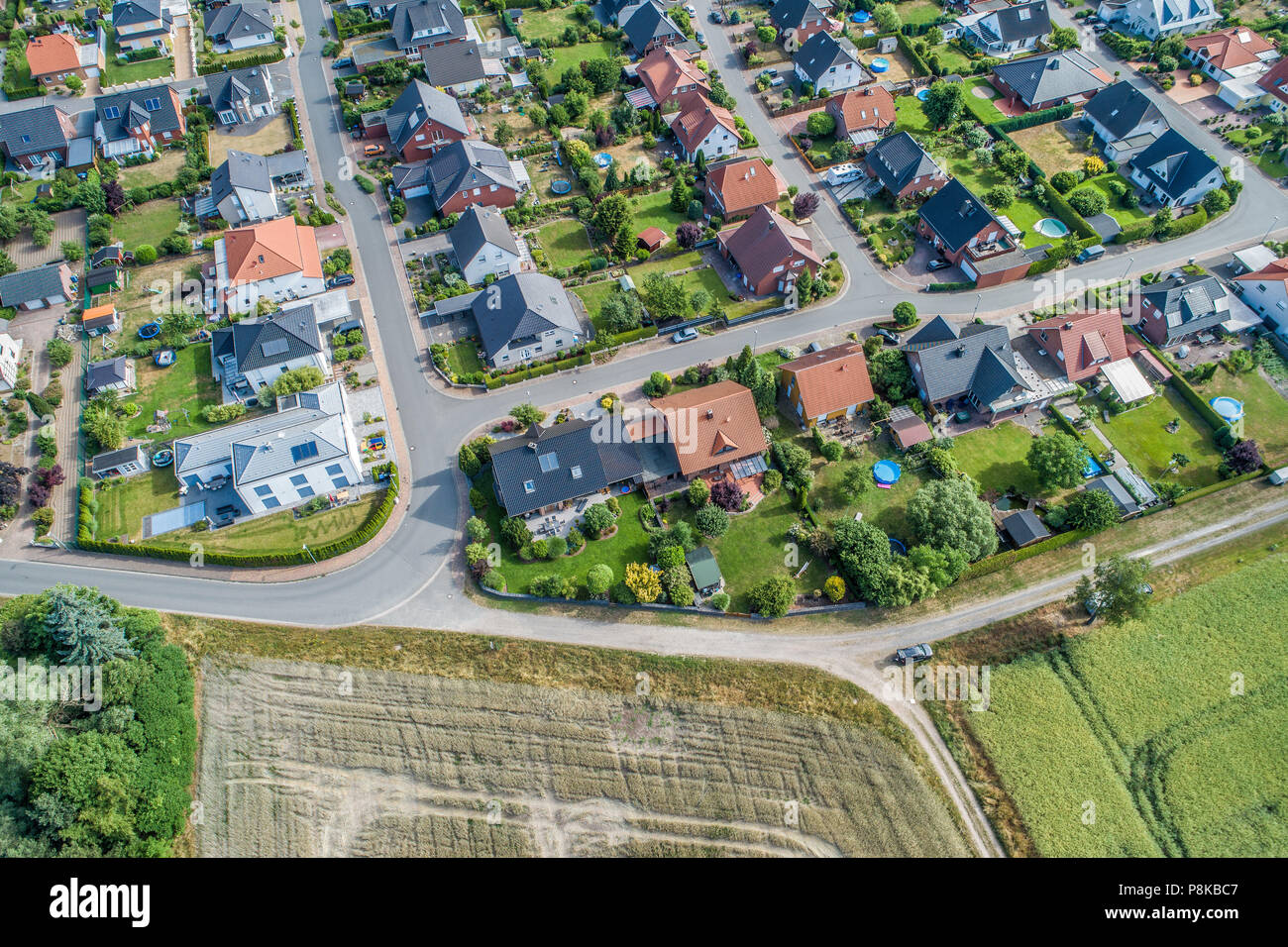 Typical German new housing development in the flat countryside of northern Germany between fields and meadows, made with drone - Stock Image