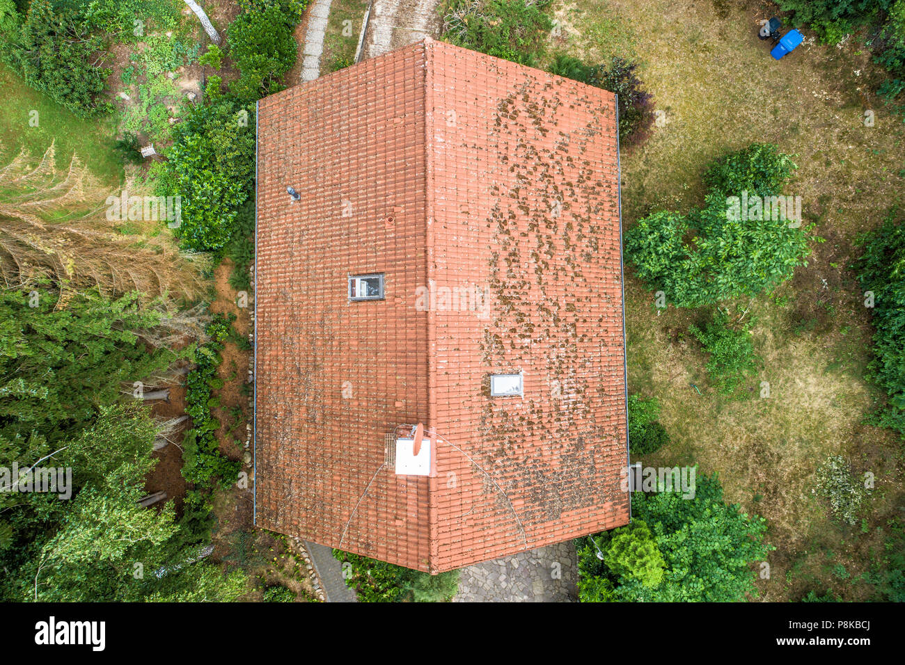 Flight over the red roof of a single family house with a chimney and a satellite antenna for inspection, control and preparation for a repair, made wi - Stock Image