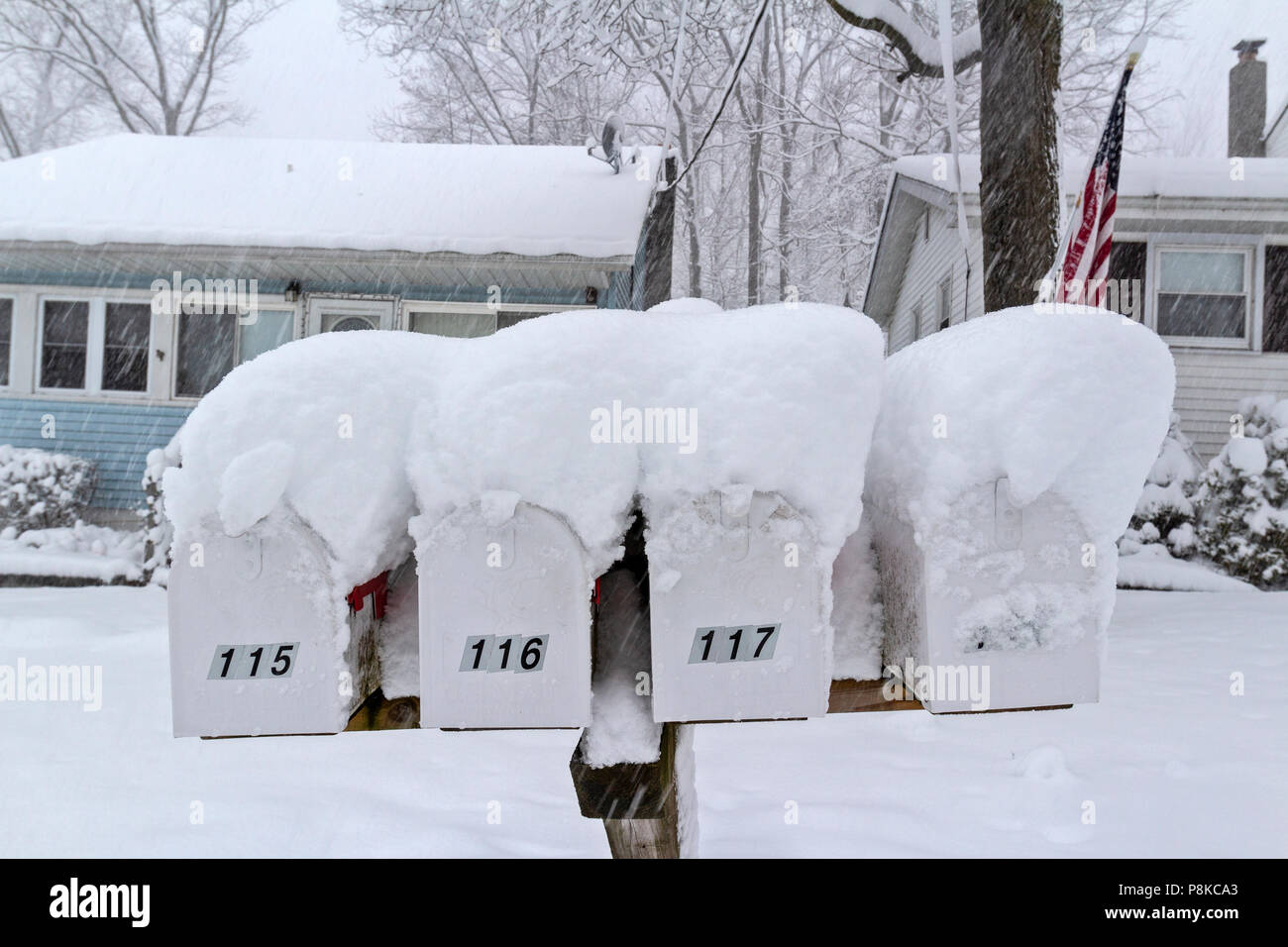 A winter snowstorm blankets a road and houses and mailboxes with freshly fallen snow. - Stock Image