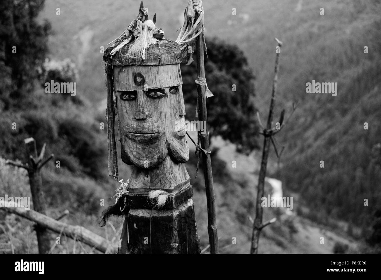 Very unusual carved WOODEN EFFIGY of NATURE SPIRIT in front of bridge in HURIKOT - EASTERN NEPAL - Stock Image