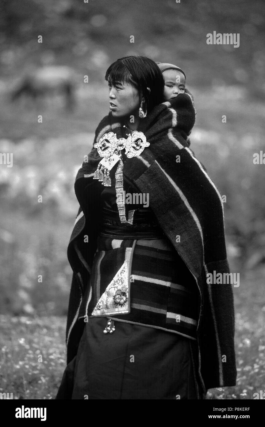 WOMAN and CHILD in DOLPO BLANKET and silver clasp at a Tibetan Buddhist FESTIVAL in DO TARAP VALLEY - DOLPO, NEPAL - Stock Image