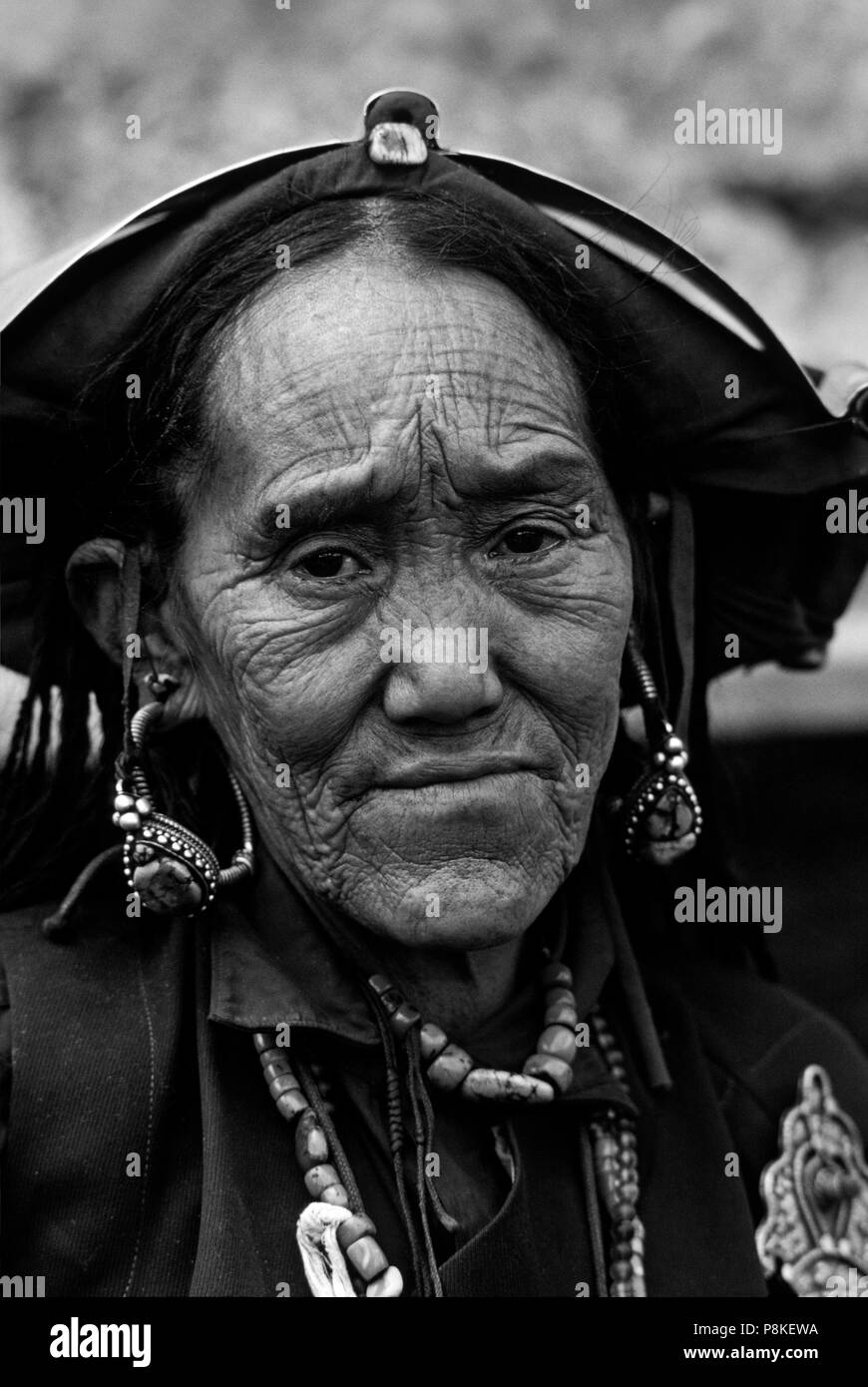 WOMAN with old style HEAD PEICE and silver clasp at a Tibetan Buddhist FESTIVAL in the DO TARAP VALLEY - DOLPO DISTRICT, NEPAL - Stock Image