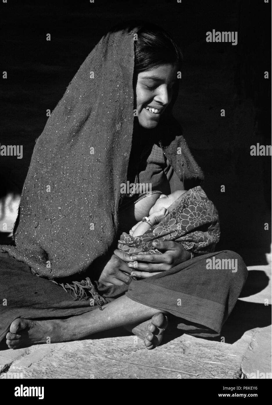A NEPALI WOMAN of the CHETRI tribe NURSES her BABY - ANNAPURNA REGION,  NEPAL Stock Photo