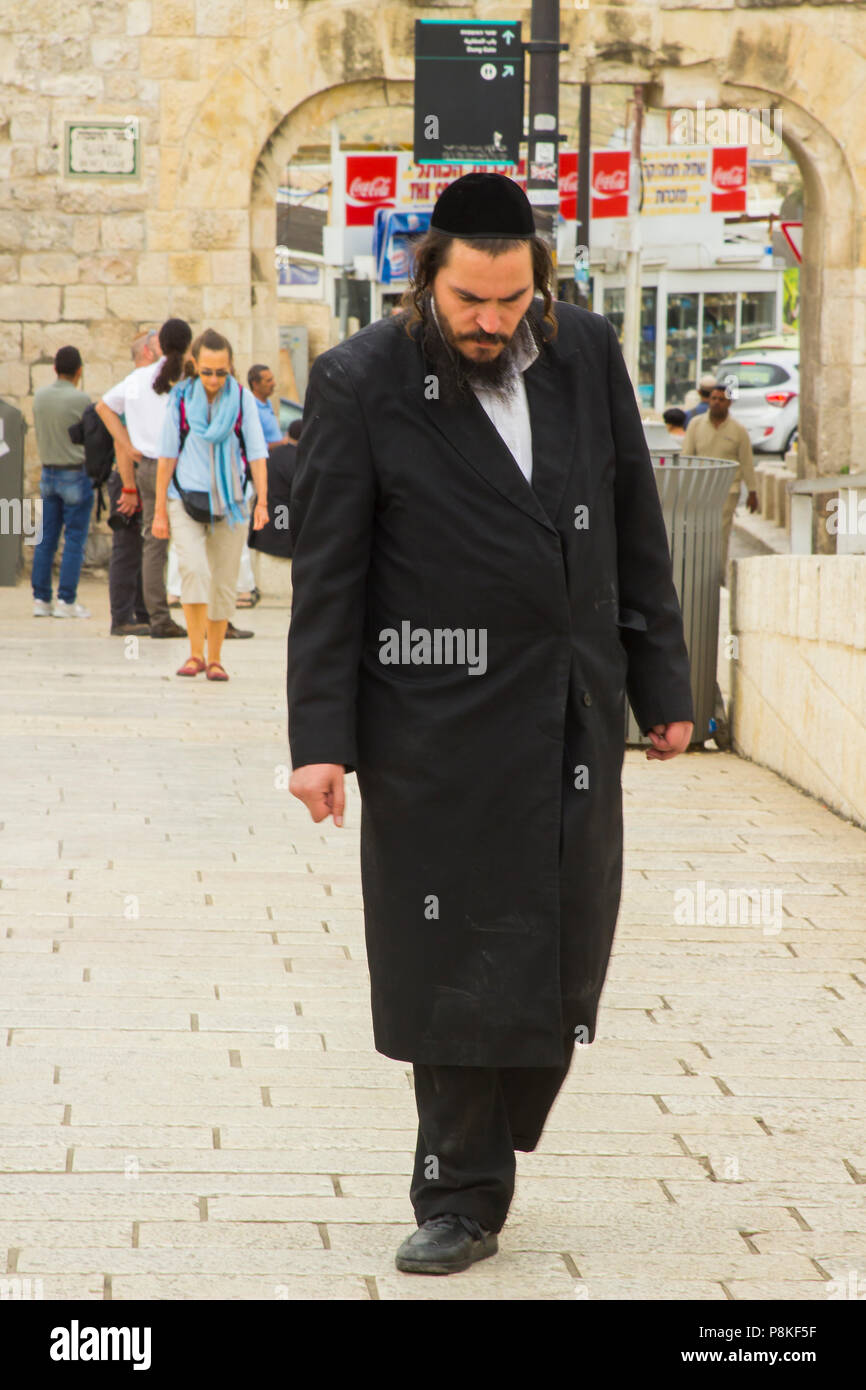 A bearded Orthodox Hasidic Jew in traditional clothing on foot and heading toward the Western Wall Jerusalem Israel for prayers. - Stock Image