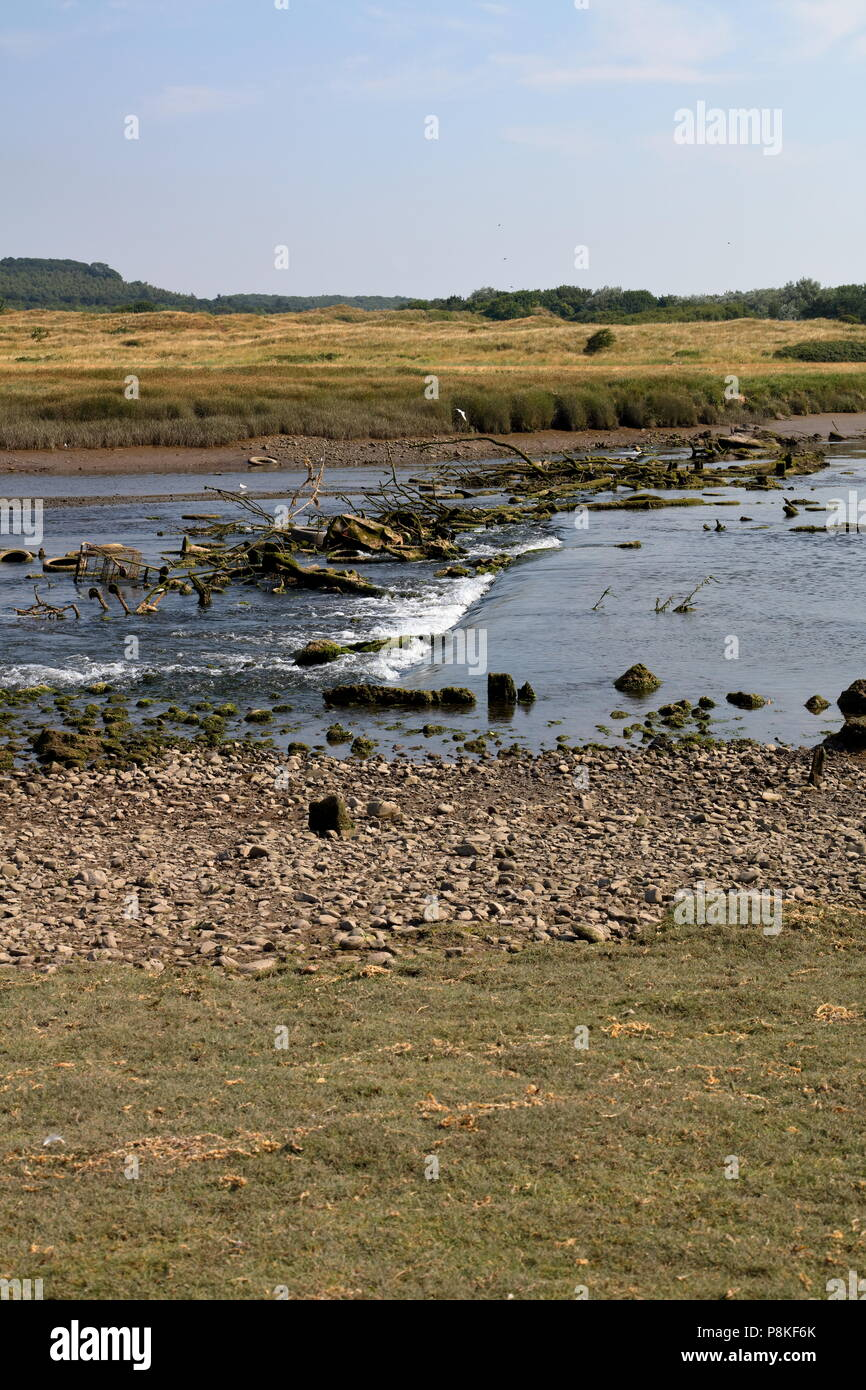 A small section of the Ogmore river with an old ruined wooden weir that has got jammed up with fallen trees and general detritus polluting the water. - Stock Image