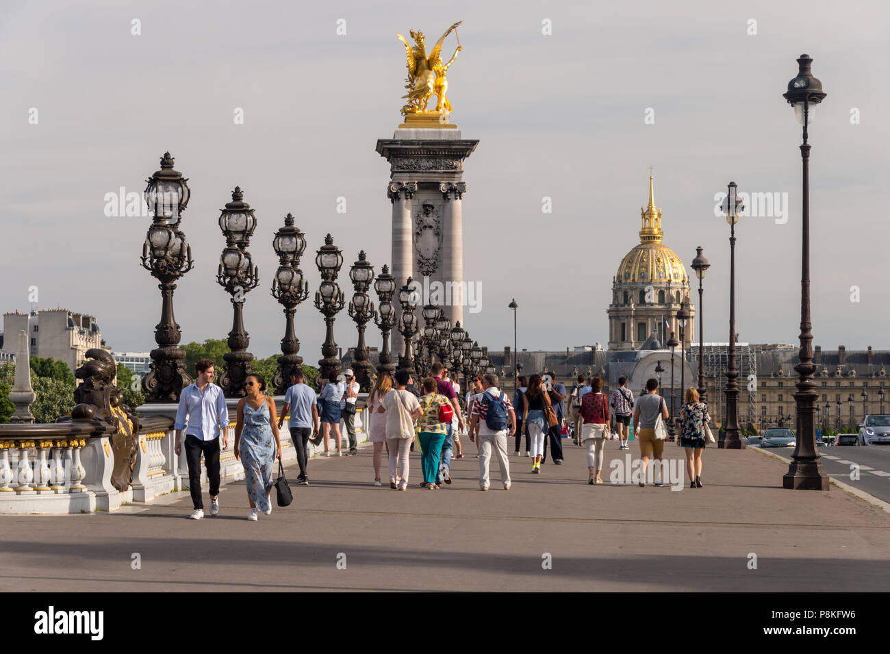 Paris, France - 24 June 2018: People walking on Alexandre III bridge and the dome of the Invalides in the bakcground. Stock Photo