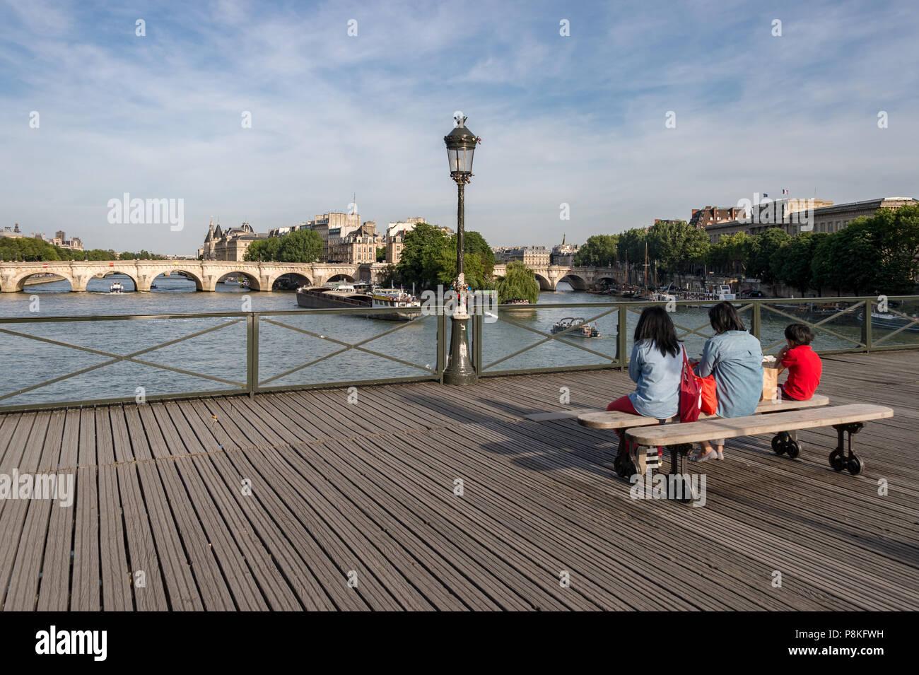 Paris, 24 June 2018: Tourists enjoying the view from Pont des Arts bridge. - Stock Image