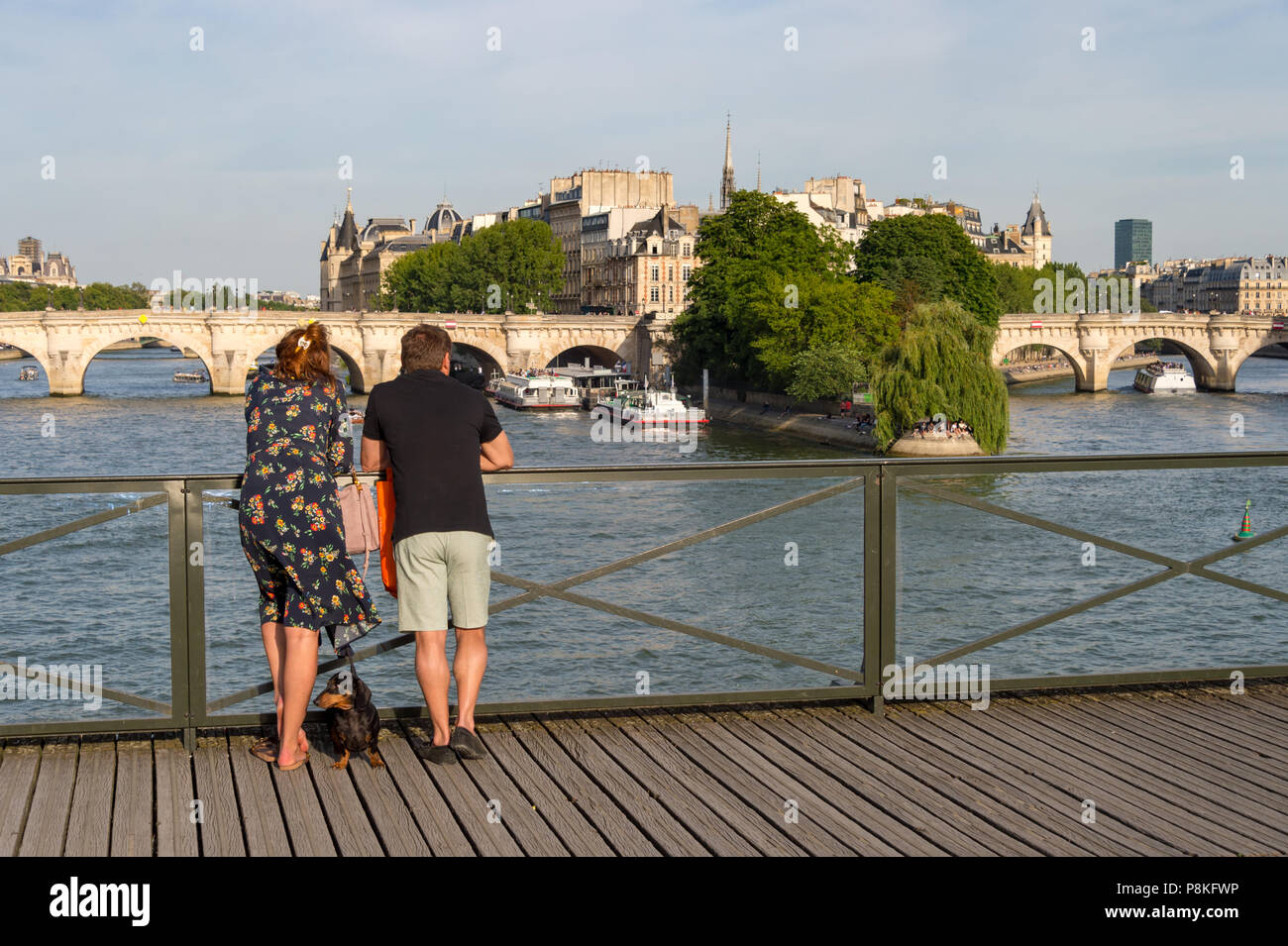 Paris, 24 June 2018: Tourists enjoying the view from Pont des Arts bridge. Stock Photo