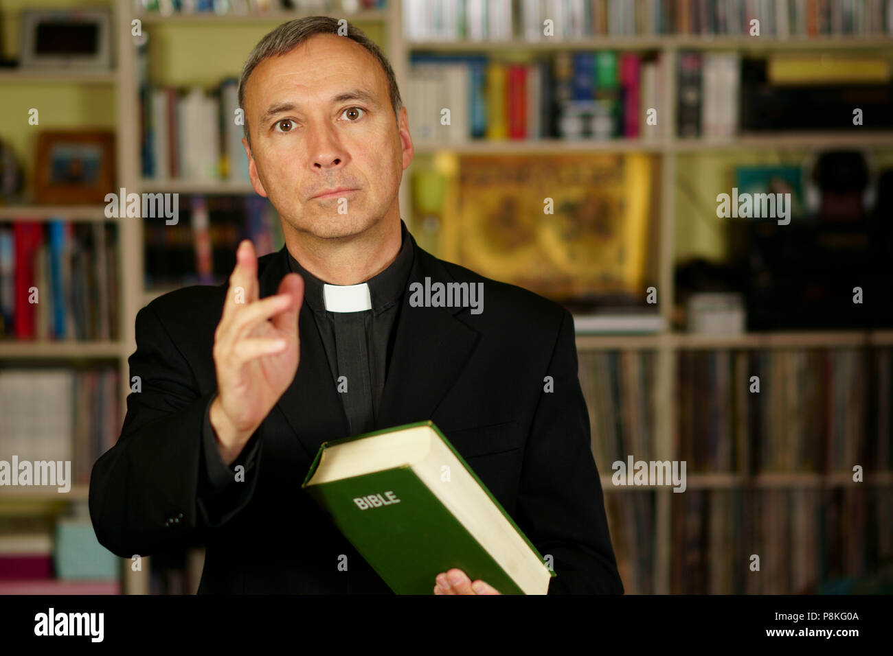 A good looking catholic priest is giving the blessing into his library. He seriously looks at us with  interest, disapproval, judgement, pensiveness a - Stock Image