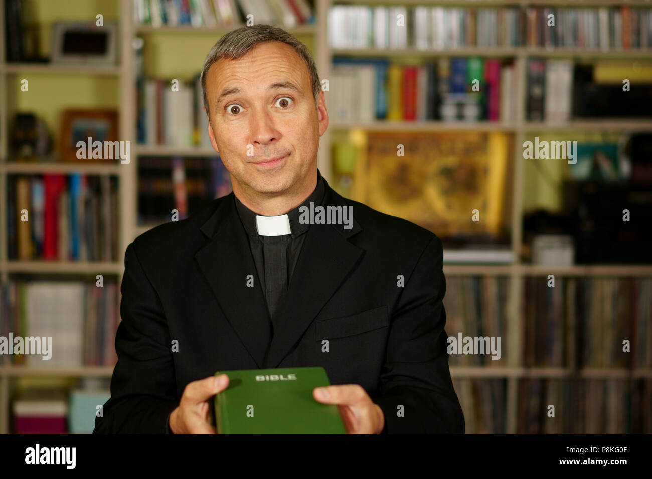 A good looking catholic priest is trying to convince us into his library. He seriously looks at us with  interest, pensiveness and proselytising. - Stock Image