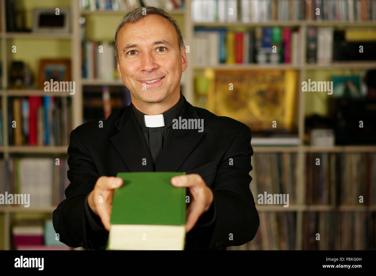 A good looking catholic priest is studying into his library. He looks at us with serenity, optimism and is offering the Bible. - Stock Image