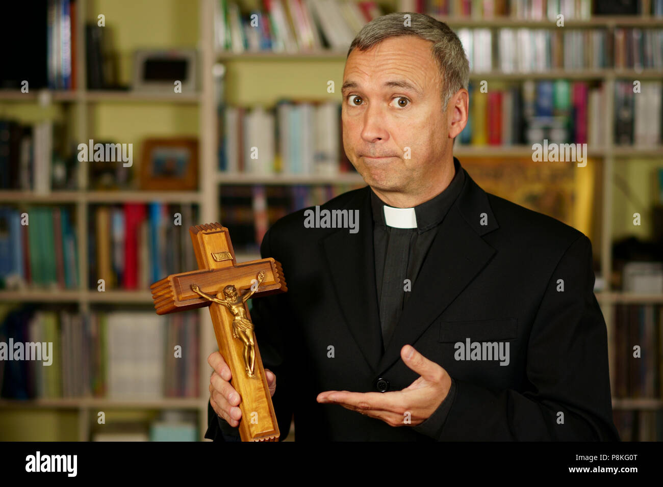 A good looking catholic priest is showing a crucifix. He seriously looks at us with interest, pensiveness and proselytising. - Stock Image